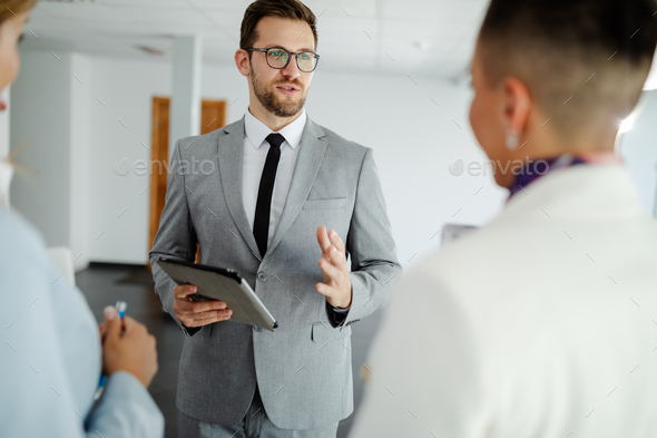 photo of young businessman explaining presentation to his colleagues before the public presentation. - Stock Photo - Images
