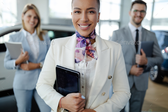 salesteam in dealership, three beautiful consultants or managers in elegant suit looking on camera. - Stock Photo - Images