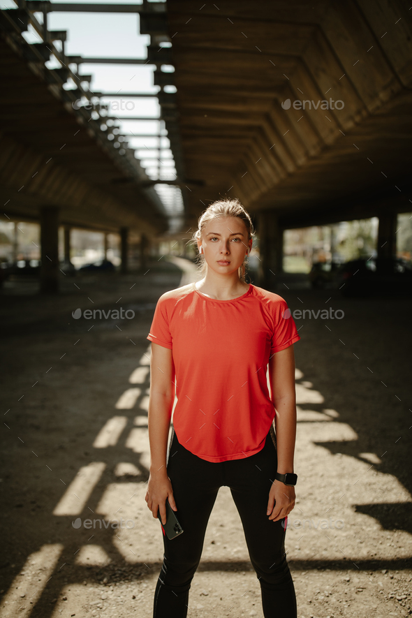Be motivated! Beautiful sexy fitness woman wearing sportswear posing under the bridge. - Stock Photo - Images