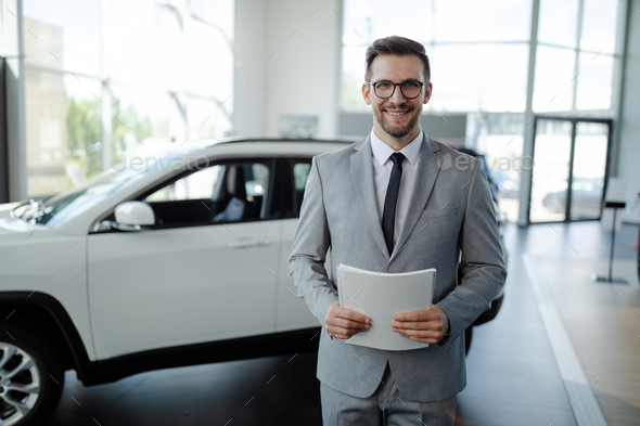 Confident young car dealer standing in showroom and holding a paper while posing. - Stock Photo - Images