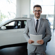 Confident young car dealer standing in showroom and holding a paper while posing. - PhotoDune Item for Sale