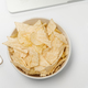 Workspace with laptop, crumpled paper, stationery and chips on white table. Bad habits concept - PhotoDune Item for Sale