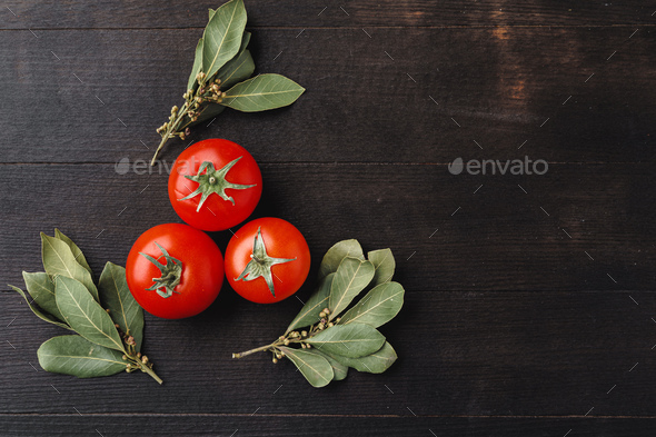 Tomatoes and bunches of dried bay leaves on dark wooden table - Stock Photo - Images