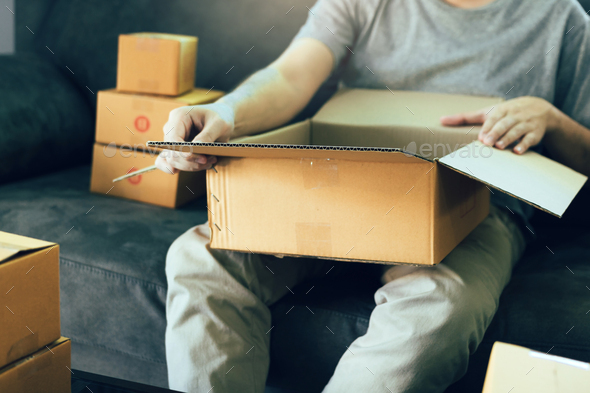 entrepreneur teenager is opening a cardboard box in order to put the product that the customer - Stock Photo - Images