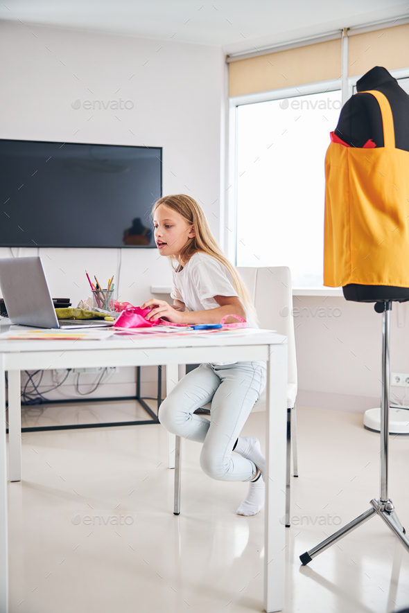 Young stylist searching for creative ideas on her gadget - Stock Photo - Images