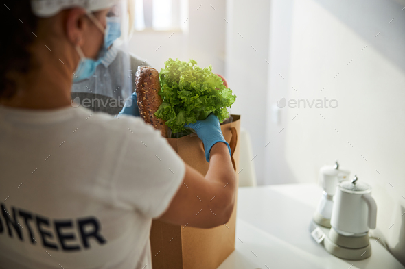 Caregiver taking the delivered foodstuffs out of the paper bag - Stock Photo - Images