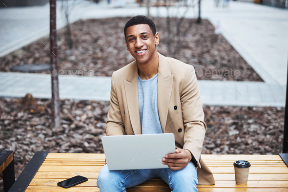Delighted young man posing on camera outside - Stock Photo - Images