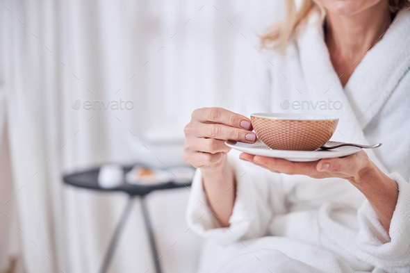 Female enjoying delicious cup of tea in spa resort hotel - Stock Photo - Images