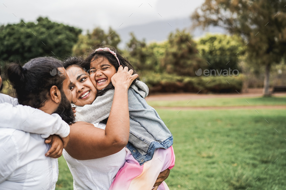 Happy indian family having fun outdoor at city park - Main focus on girl face - Stock Photo - Images