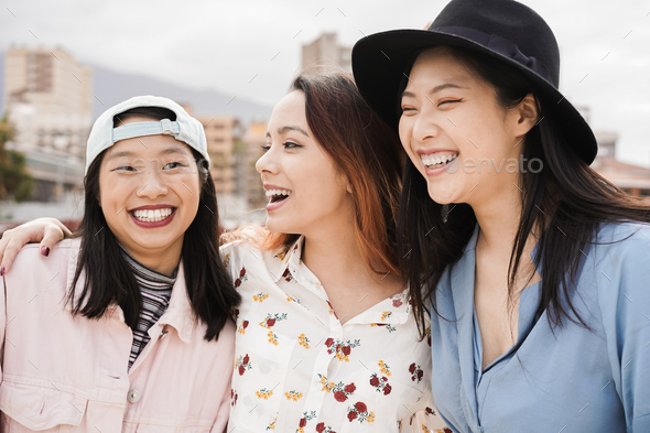 Happy asian girls having fun together outdoor around city - Main focus on center woman face - Stock Photo - Images