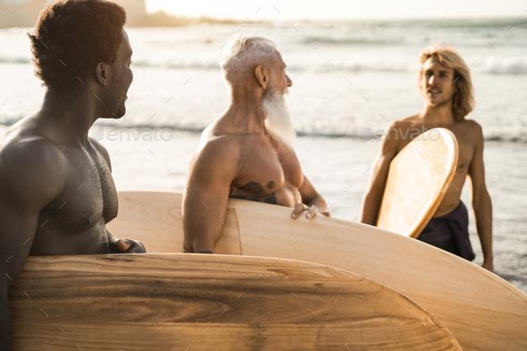 Multi generational surfer men having fun on the beach - Main focus on african man - Stock Photo - Images