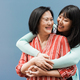Asian mother and daughter having fun outdoor with blue background - Main focus on mother face - PhotoDune Item for Sale