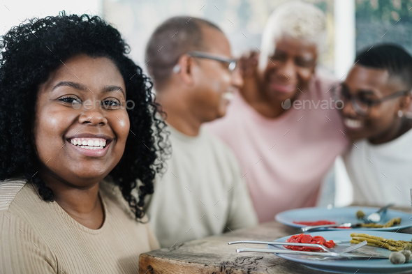 Happy black young woman eating lunch with her family at home - Focus on girl face - Stock Photo - Images