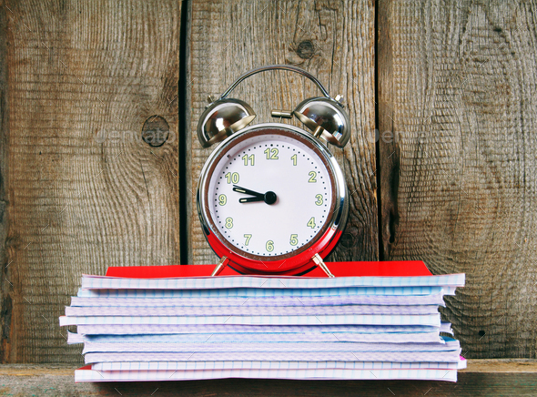Writing-books and an alarm clock . - Stock Photo - Images