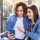 Arab couple looking at pictures taken with their smartphone outdoors - PhotoDune Item for Sale