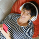 Woman smiling looking at her smartphone while listening to music with headphones - PhotoDune Item for Sale