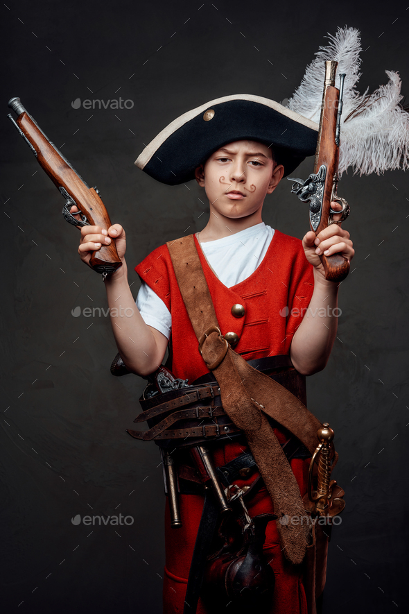 Small boy wearing pirate hat and costume with guns - Stock Photo - Images