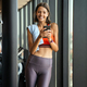 Portrait of a cheerful sports woman using smartphone in fitness gym - PhotoDune Item for Sale
