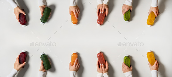 Hands holding fresh natural organic juices in bottles, copy space - Stock Photo - Images