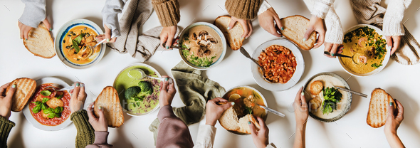 People eating various Autumn and Winter creamy vegan soups together - Stock Photo - Images