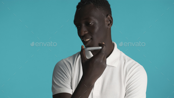Young African American man recording voice message using smartphone over colourful background - Stock Photo - Images