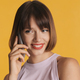 Pretty smiling girl with bob hair talking with best friend on phone over colorful background - PhotoDune Item for Sale