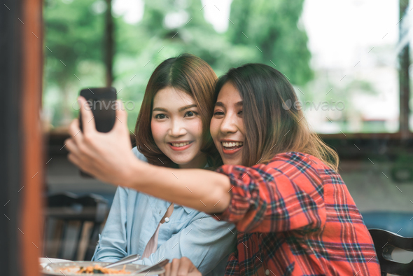 Asian women lesbian lgbt couple eating at restaurant or cafe. - Stock Photo - Images