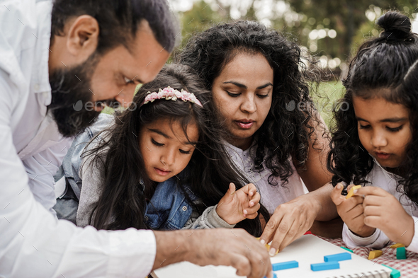 Indian parents having fun at city park playing with wood toys with their daughter and son - Stock Photo - Images