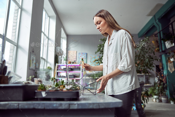 confident florist is working with composition made from glass stones and plants - Stock Photo - Images