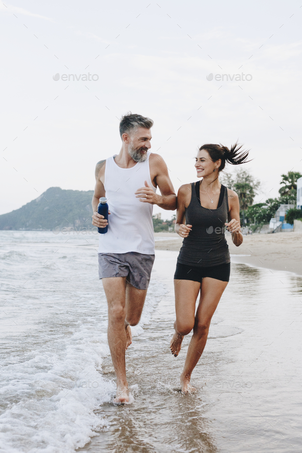 Couple jogging on a beach - Stock Photo - Images