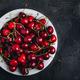 Cherry. Sweet Cherries in bowl on dark stone concrete background. Ripe Sweet Red Cherries. - PhotoDune Item for Sale