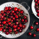 Cherry. Sweet Cherries in white colander on dark stone concrete background. Ripe Sweet Red Cherries. - PhotoDune Item for Sale