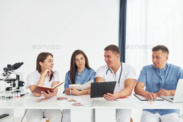 Sitting by the table. Group of young doctors is working together in the modern office - Stock Photo - Images