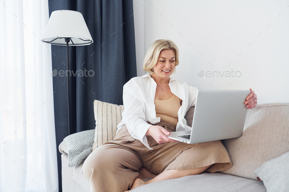 Middle-aged woman in elegant clothes is at home with laptop - Stock Photo - Images