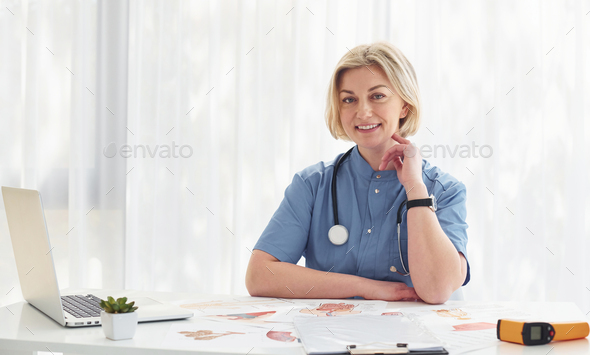 In the cabinet. Middle-aged professional female doctor in uniform and with stethoscope - Stock Photo - Images