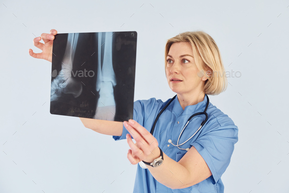 Holds x-ray. Middle-aged professional female doctor in uniform and with stethoscope - Stock Photo - Images
