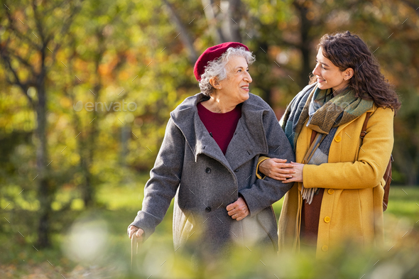 Senior woman walking with granddaughter in park during autumn - Stock Photo - Images