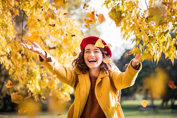 Young playful woman playing with leaves in autumn - Stock Photo - Images