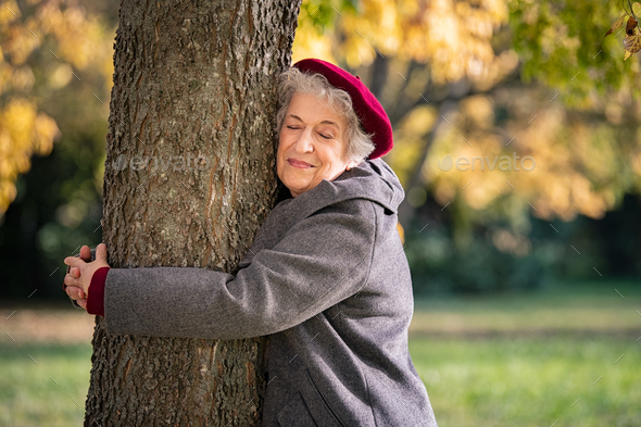 Senior woman hugging tree - Stock Photo - Images