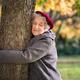 Senior woman hugging tree - PhotoDune Item for Sale