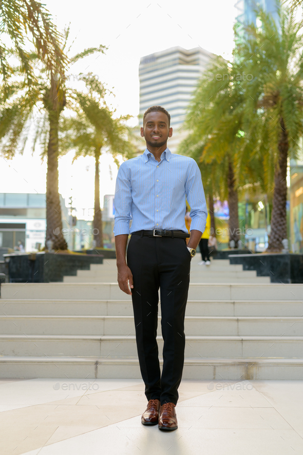 Full length shot of handsome black African businessman outdoors in city during summer smiling and - Stock Photo - Images