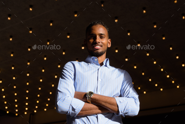 Low angle view shot of handsome black African businessman outdoors in city during summer smiling - Stock Photo - Images