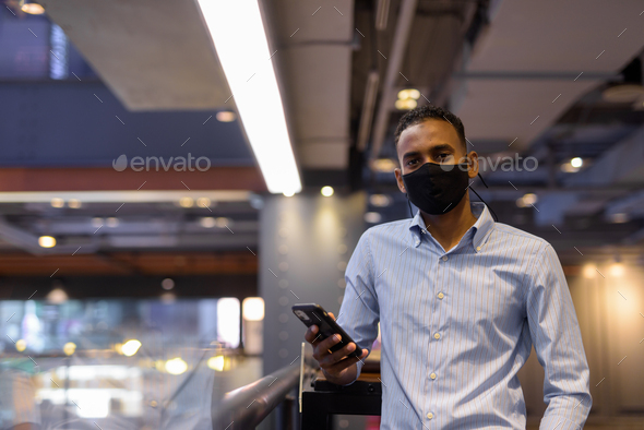 Portrait of handsome black African businessman inside shopping mall wearing face mask and using - Stock Photo - Images