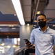 Portrait of handsome black African businessman inside shopping mall wearing face mask and using - PhotoDune Item for Sale