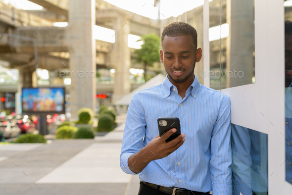 Portrait of handsome black African businessman outdoors in city during summer using mobile phone - Stock Photo - Images