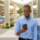 Portrait of handsome black African businessman outdoors in city during summer using mobile phone - PhotoDune Item for Sale