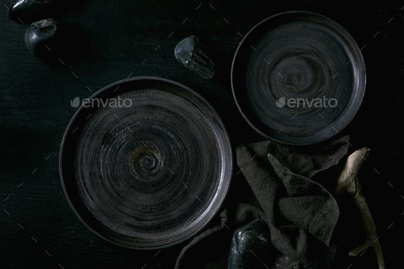 Empty black ceramic plates with black stones - Stock Photo - Images