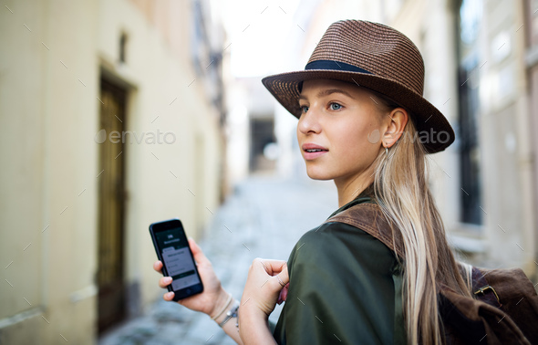 Young woman traveler in city on holiday using smartphone, sightseeing - Stock Photo - Images