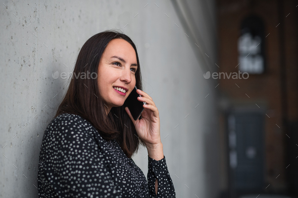 Portrait of mid adult businesswoman standing indoors in office, using smartphone - Stock Photo - Images