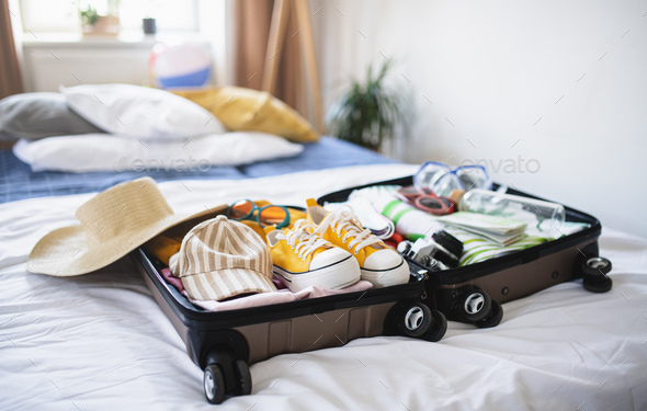 Open suitcase packed for holiday on bed at home, coronavirus concept - Stock Photo - Images